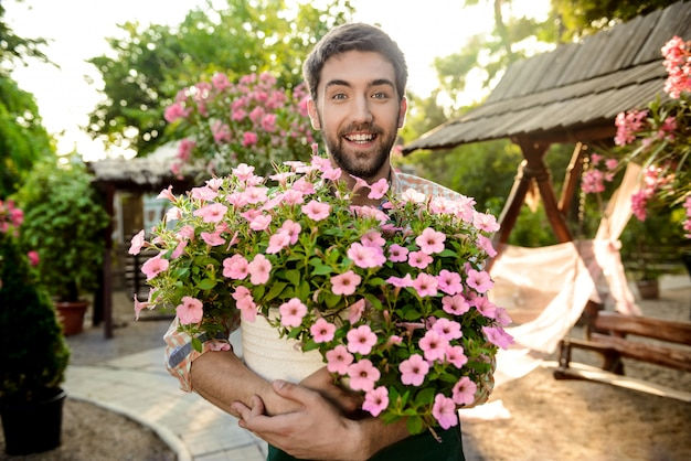 Young handsome cheerful gardener smiling, holding big pot with flowers