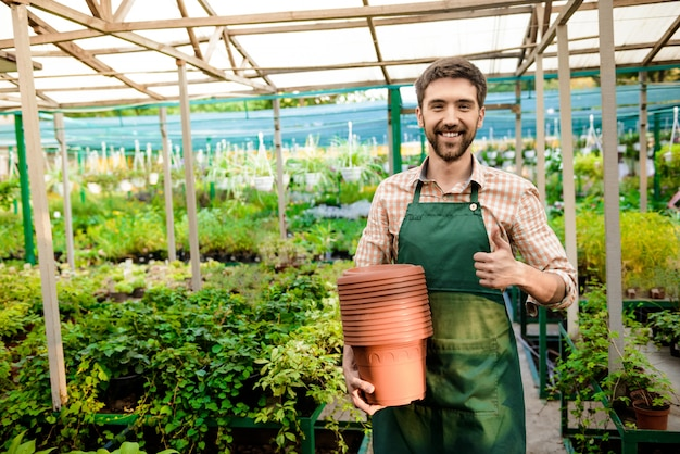 Young handsome cheerful gardener smiling, holding pots, showing okay among plants