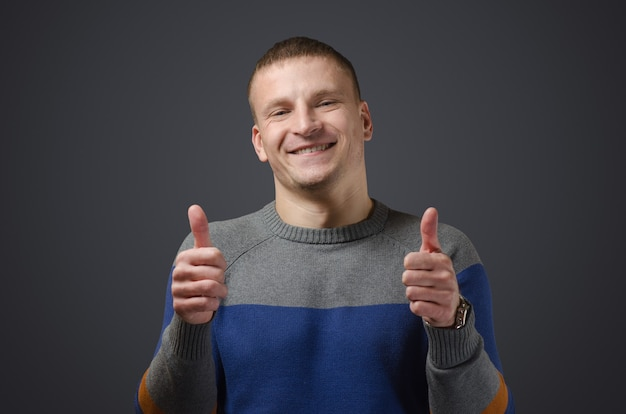 「親指を立てる」ことを示す若いハンサムで陽気な男。黒い表面のスタジオでの感情的な写真。