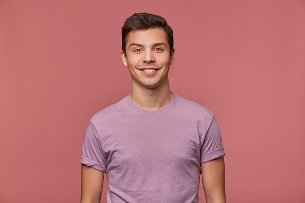 若いハンサムな陽気な男は、空白のtシャツを着て、幸せな表情でカメラを見て、ピンクの背景の上に立っています。