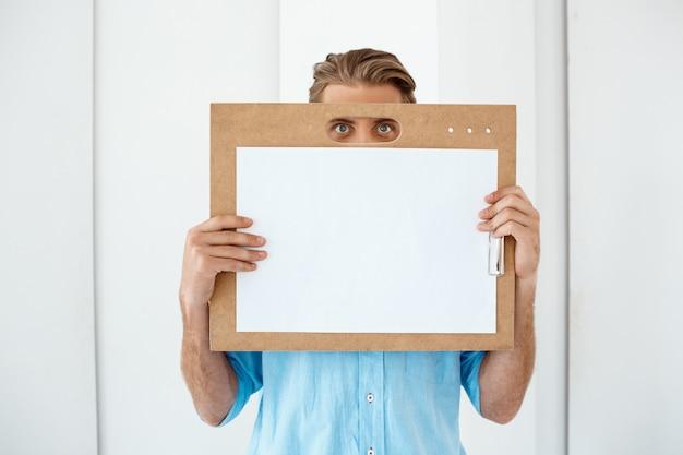 Молодой красивый жизнерадостный усмехаясь бизнесмен стоя на таблице держа деревянную доску сзажимом для бумаги с белым листом. светлый современный офисный интерьер