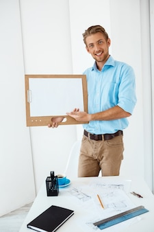 Young handsome cheerful smiling businessman standing at table holding wooden clipboard with white sheet pointing on it. light modern office interior