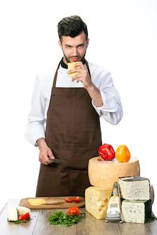 白で隔離された、さまざまな種類のチーズで作る若いハンサムなシェフの料理人