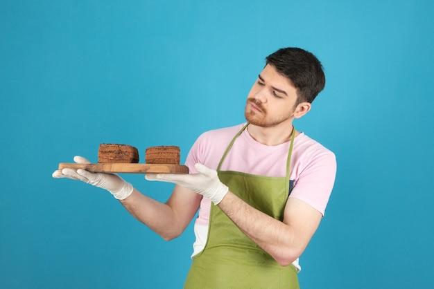 青にチョコレートケーキのスライスを保持している若いハンサムなシェフ。