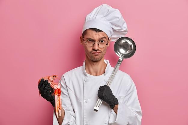 Молодой красивый шеф-повар держит сырые раки изолированными