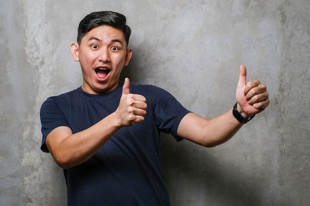 コンクリートの壁の背景の上にカジュアルなtシャツを着ている若いハンサムな中国人男性は、手で前向きなジェスチャーをすることを承認し、笑顔で成功を喜んで親指を立てます。勝者のジェスチャー。