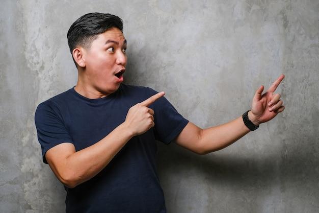 笑みを浮かべて、コンクリートの壁の背景の上の側に両手と指で指しているカメラを見て海軍のtシャツを着て若いハンサムな中国人男性