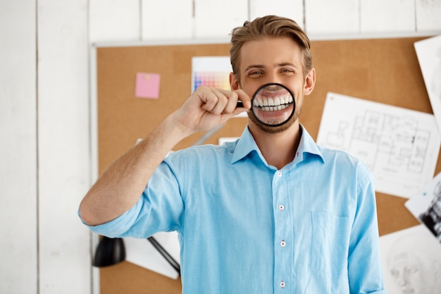Young handsome confident funny businessman standing over cork board holding magnifier. . white modern office interior