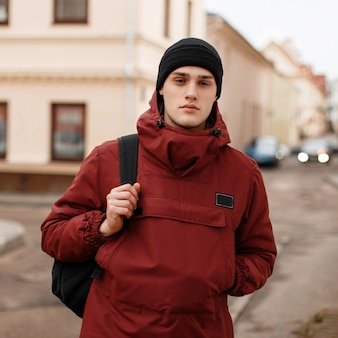 Young handsome confident man in a black knitted hat in a trendy red long jacket with a black backpack is standing outdoors near vintage buildings