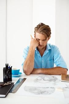 Молодой красивый уверенно задумчивый бизнесмен сидя на таблице думая над портретом чертежа карандаша. белый современный офисный интерьер.