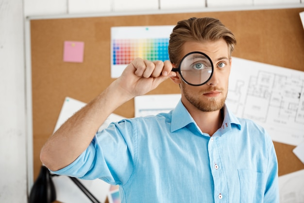 Young handsome confident pensive businessman standing over cork board  through magnifier. white modern office interior