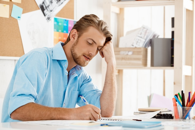 Young handsome confident pensive businessman working sitting at table writing in notepad. white modern office interior