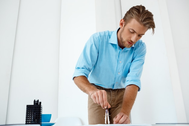 Young handsome confident pensive businessman working standing at table drawing sketch. white modern office interior