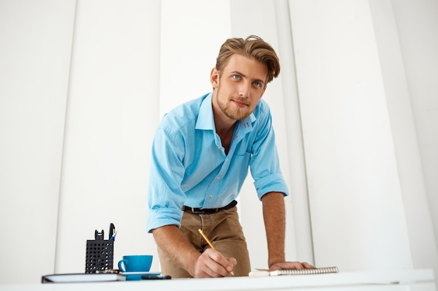 Young handsome confident pensive businessman working standing at table over notepad looking. white modern office interior.