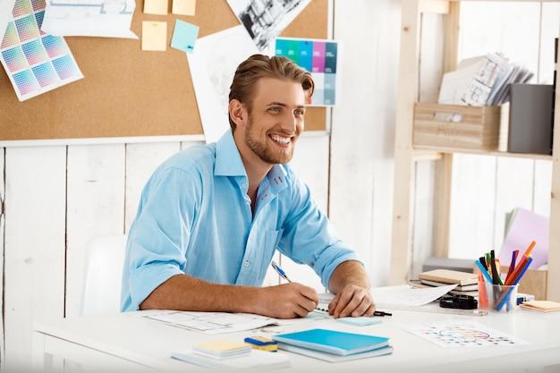 Сидеть молодого красивого уверенно усмехаясь бизнесмена работая на сочинительстве таблицы в тетради. белый современный офисный интерьер