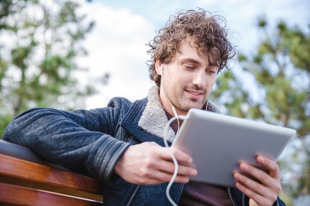 나무 벤치에 앉아 태블릿을 사용하고 이어폰을 사용하여 음악을 듣고 검은 재킷에 젊은 잘 생긴 콘텐츠 곱슬 남자