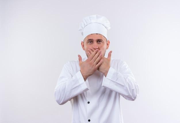Giovane cuoco bello in bocca di chiusura uniforme del cuoco unico con le mani isolate su spazio bianco