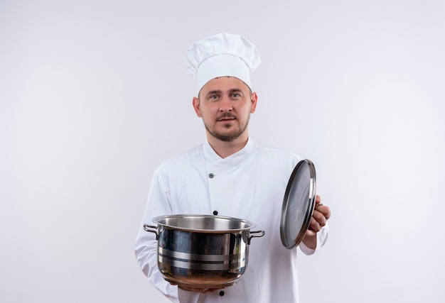 Young handsome cook in chef uniform holding boiler and its cover looking  on isolated white space