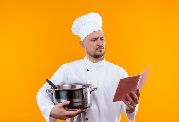 Young handsome cook in chef uniform holding boiler and note pad and looking at note pad on isolated orange space