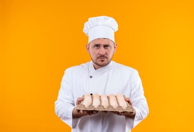 Giovane cuoco bello in cartone uniforme della holding del cuoco unico delle uova che sembrano isolate sullo spazio arancione