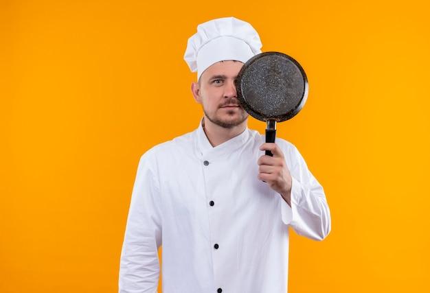 Giovane cuoco bello in uniforme del cuoco unico che tiene la padella e che si nasconde dietro esso che sembra isolato sullo spazio arancione