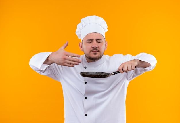Giovane cuoco bello in uniforme del cuoco unico che tiene la padella e annusando con gli occhi chiusi e la mano alzata isolata sullo spazio arancione