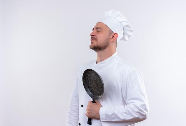Giovane cuoco bello in uniforme del cuoco unico che tiene padella in piedi in vista di profilo con gli occhi chiusi isolati su uno spazio bianco