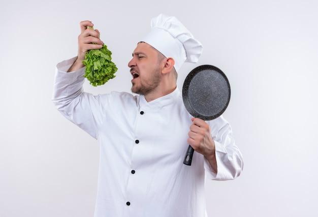 Giovane cuoco bello in uniforme del cuoco unico che tiene lattuga e padella cercando di mordere la lattuga su uno spazio bianco isolato