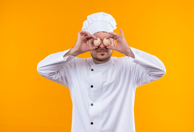Young handsome cook in chef uniform putting eggs on eyes isolated on orange space