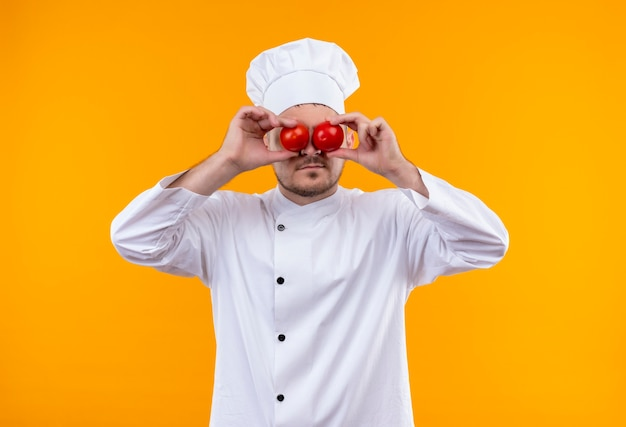 Young handsome cook in chef uniform putting tomatoes on eyes isolated on orange space