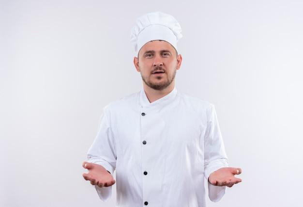 Giovane cuoco bello in uniforme del cuoco unico che mostra le mani vuote che sembrano isolate sullo spazio bianco