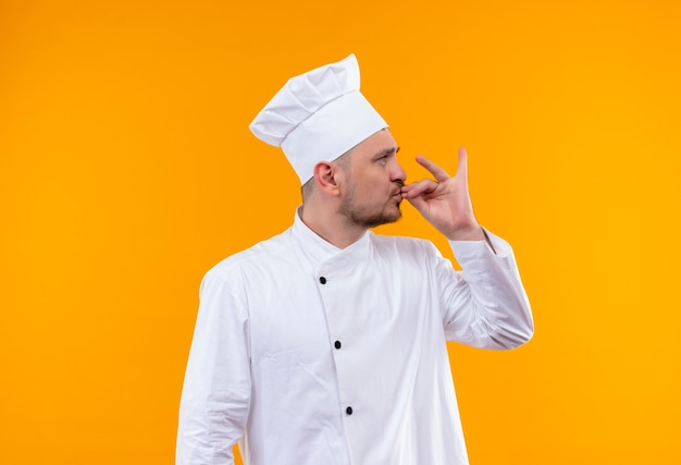 孤立したオレンジ色の空間で横を見ておいしいジェスチャーをしているシェフの制服を着た若いハンサムな料理人