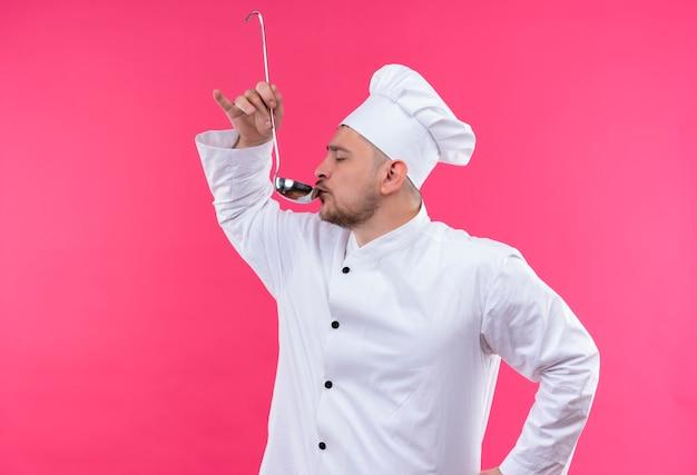 ピンクのスペースで隔離のお玉から飲むシェフの制服を着た若いハンサムな料理人