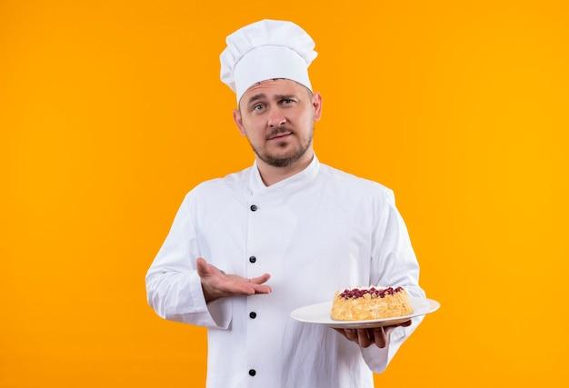 オレンジ色のスペースで隔離のケーキのプレートを保持し、指しているシェフの制服を着た若いハンサムな料理人