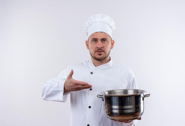 シェフの制服を着た若いハンサムな料理人が白いスペースに孤立して見える鍋を保持し、指しています