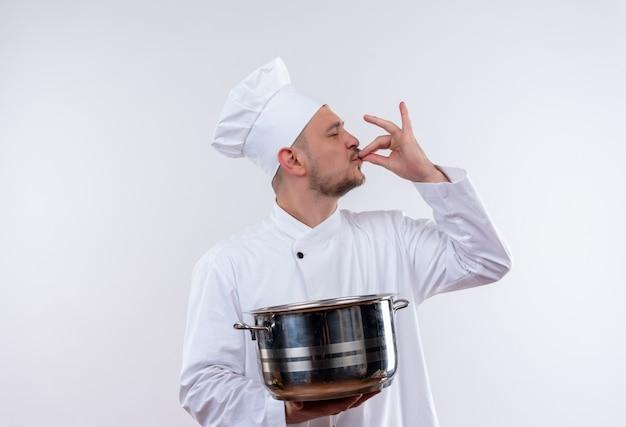 ボイラーを保持し、孤立した白いスペースでおいしいジェスチャーをしているシェフの制服を着た若いハンサムな料理人
