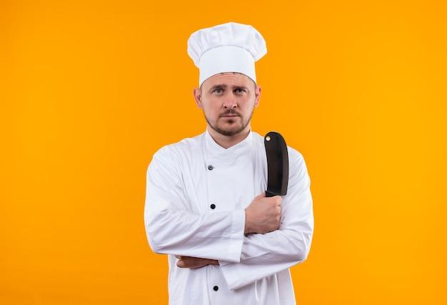 オレンジ色のスペースで孤立して見える包丁を保持しているシェフの制服を着た若いハンサムな料理人