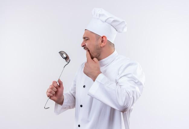 それを見て、孤立した白いスペースで口に指を置くシェフの制服を着た若いハンサムな料理人