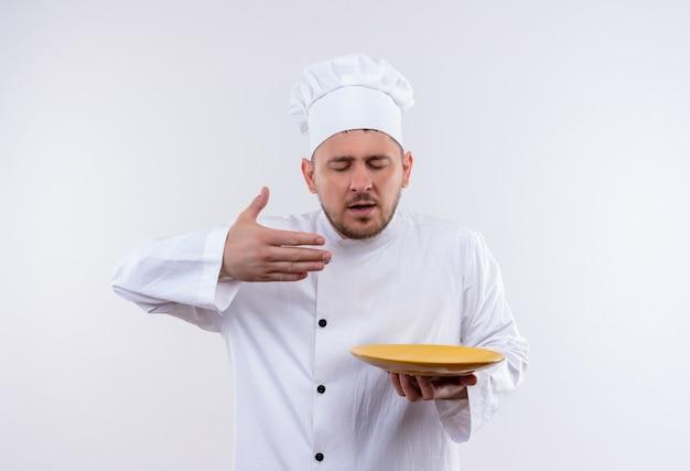 プレートを保持し、白いスペースで隔離の上げられた手と目を閉じてスニッフィングシェフの制服を着た若いハンサムな料理人