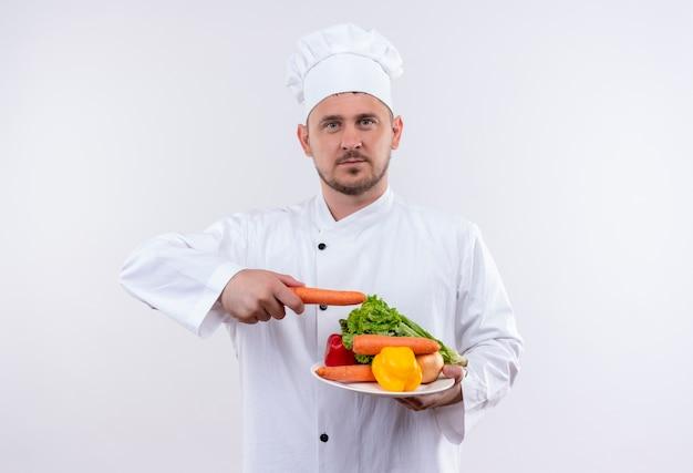 野菜とプレートを保持し、孤立した白いスペースを見てニンジンでそれらを指しているシェフの制服を着た若いハンサムな料理人