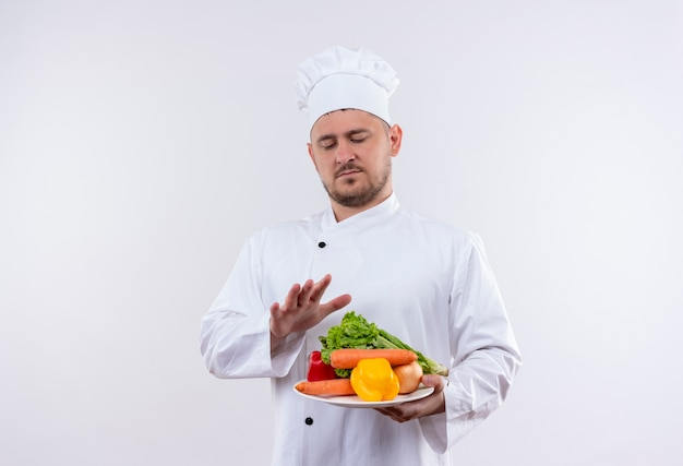 シェフの制服を着た若いハンサムな料理人は、野菜がそれらを見て、孤立した白いスペースでそれらの上に手を保つとプレートを保持しています