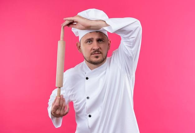 Молодой красивый повар в униформе шеф-повара держит скалку, глядя изолированно на розовом пространстве