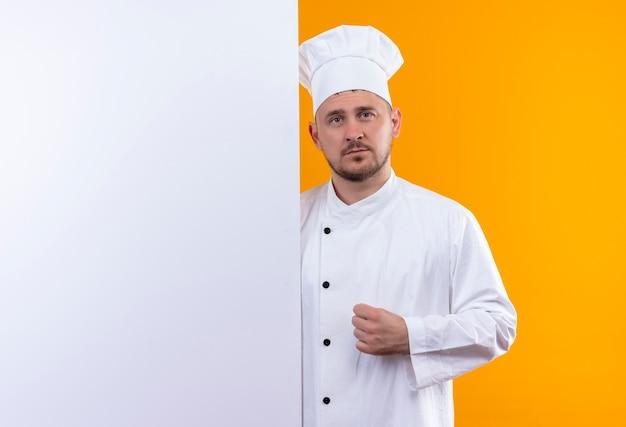 オレンジ色のスペースでまっすぐに孤立して見える白い壁の後ろに立っているシェフの制服を着た若いハンサムな料理人