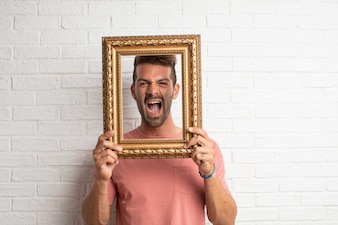 Young handsome cool man  joking with a baroque frame