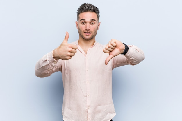 Young handsome cool man showing thumbs up and thumbs down, difficult choose concept