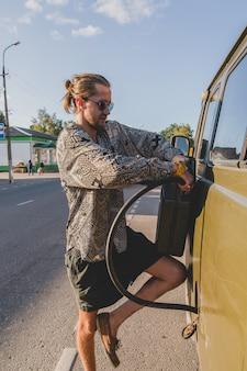 お団子の髪型が古いソビエト車に燃料を充填する若いハンサムな田舎の男。
