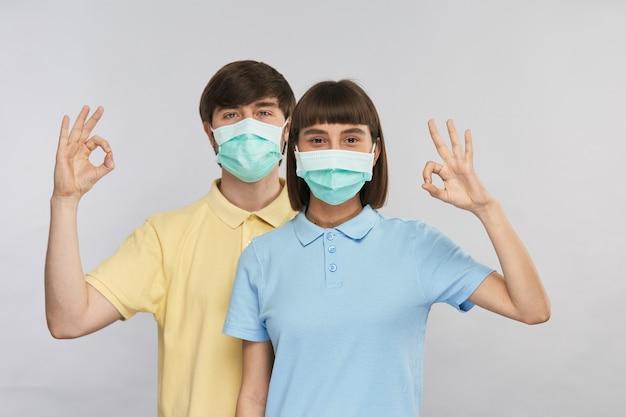 Молодая красивая пара мужчина и женщина в защитных масках, показывающая жест ок, копировальное пространство, счастливые изолированные и защищенные лица, в безопасности от коронавируса с маской