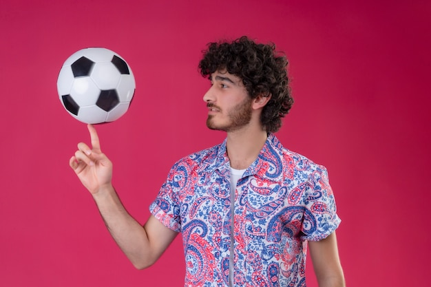 Giovane uomo riccio bello che tiene il pallone da calcio sul dito e guardandolo sulla parete rosa isolata