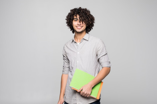 孤立した白い壁の上のノートを持つ若いハンサムな巻き毛学生男