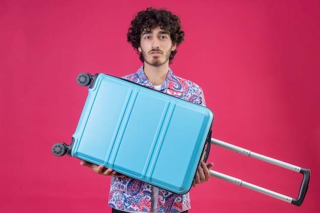 격리 된 분홍색 벽에 가방을 들고 젊은 잘 생긴 곱슬 여행자 남자